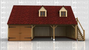 Three bay garage with room over. One garage bay secured with doors, the other two open. External oak staircase leading up to room above which has 2 dormer windows to the front.