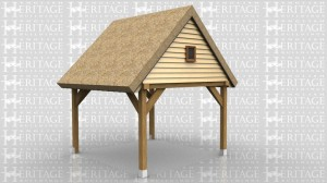 This oak frame is an open carport attached to an existing building on one side. The roof has a gable end and the roof covering is thatch. The gable is weatherboarded and has a small window in it.