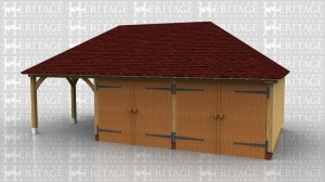 This oak framed garage building has one open bay on the left and two enclosed garage bays. The enclosed bays are accessed by a set of garage doors to the front.