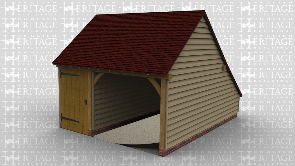 A two bay oak frame garage with a partition between the two bays, one bay has a door at the front and the other is open at the front.