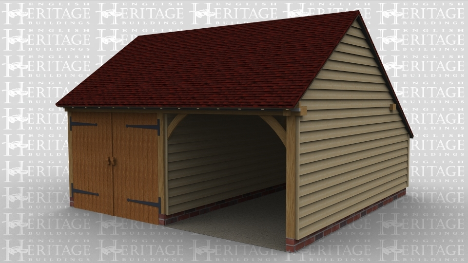 A 2 bay oak framed garage with a partition between the bays, one bay open at the front while the other has a pair of garage doors on the front.