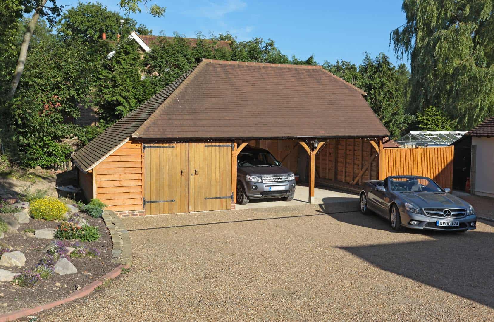 A 3 bay oak garage with luxury cars parked inside