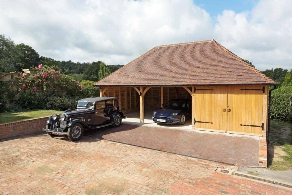 An oak framed garage with two luxury cars parked inside it