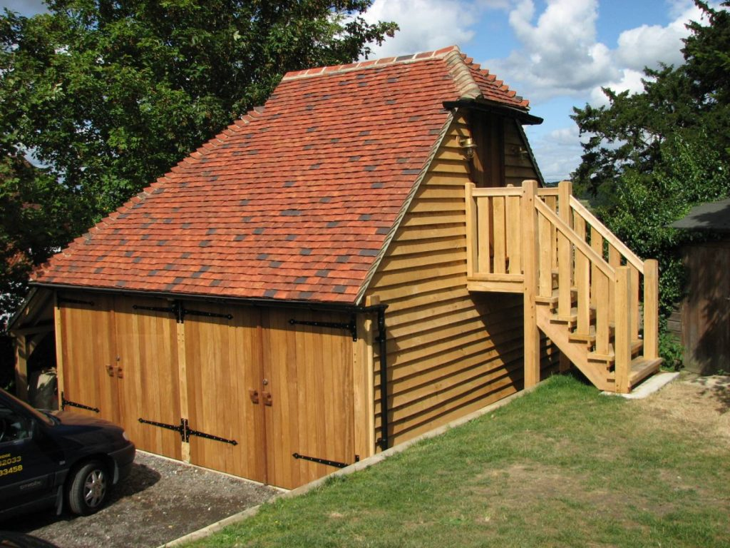 An oak framed double garage with a room above on an upper floor, accessible by exterior stairs