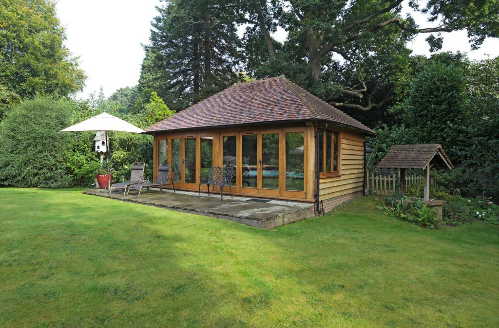 An oak framed garden room with a patio on a well-kept lawn