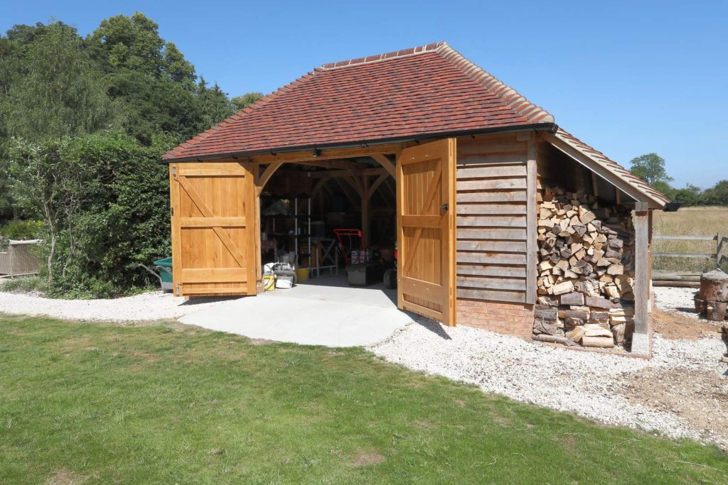 An oak framed single garage with the doors open and a wood store attached to the side